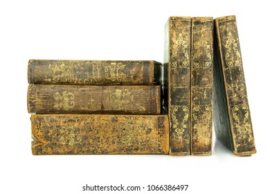 Six aged ancient old leather books stacked and standing, studio shot on white.