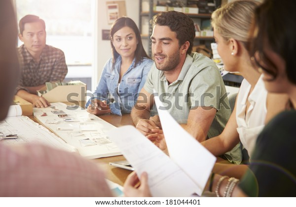 Six Architects Sitting Around Table Having Meeting