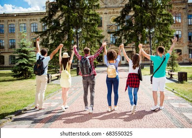 Six attractive young bachelors are near university, standing near the building, with raised arms, celebrating, wearing casual smart