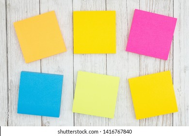 Six blank sticky notes on weathered whitewash textured wood background you can use as a mockup for your message
