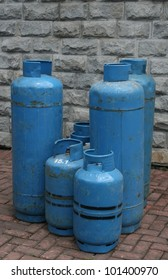 Six blue gas tanks placed at the pavement