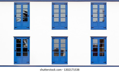 Six Blue Windows in a white facade of a building