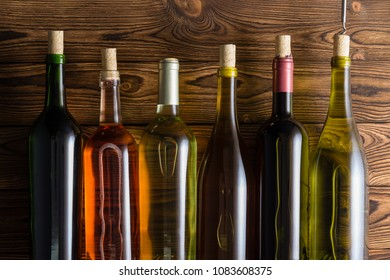 Six bottles of wine with corkscrew against wooden background