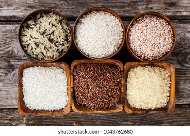 Six bowls with different varieties of rice on a wooden background, top view. Ingredient for a healthy diet.