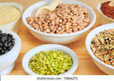 Six bowls of dry staples -- quinoa, pinto beans, black beans, rice, and peas