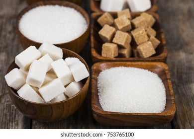 Six bowls of sugar  on an old wooden background.