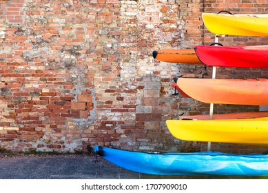 Six brightly coloured canoes stack on canoe rack against red brick wall