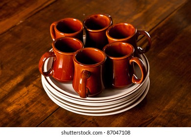 Six brown coffee mugs sitting on top of a stack of plates