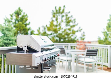 Six burner outdoor gas grill with open lid on back patio.