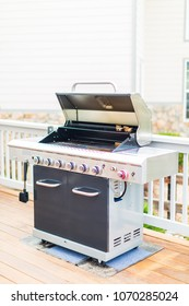 Six burner outdoor gas grill with open lid on backyard.