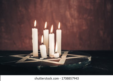 Six burning candles and the Star of David against on a red background wall.