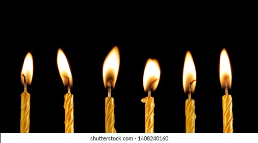 Six burning golden candles on black background with space for text