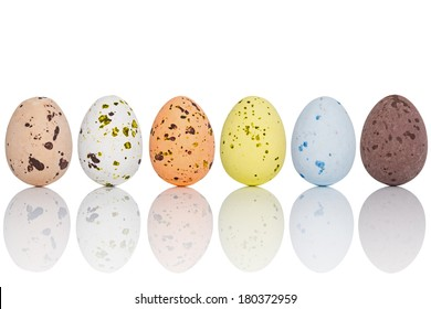 Six candy coated chocolate Easter eggs in a line, isolated on white with clipping path.