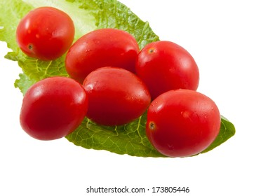 Six cherry tomatoes on a lettuce leaf