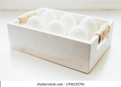 Six chicken white eggs in a wooden box on a white background - high key photo - natural light