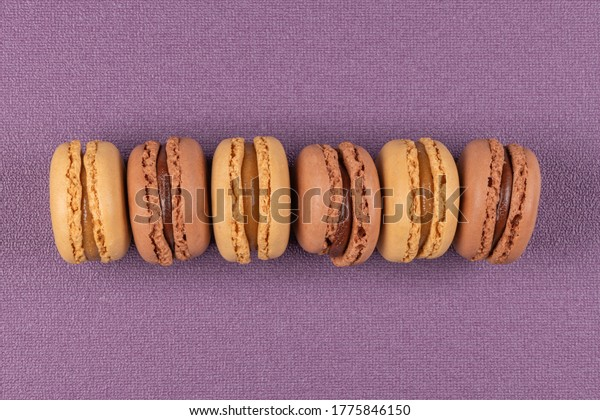 Six coffee and chocolated flavoured macaroons on purple vinyl background.