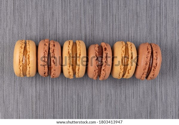 Six coffee and chocolated flavoured macaroons on grey vinyl background.