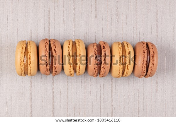 Six coffee and chocolated flavoured macaroons on beige vinyl background.