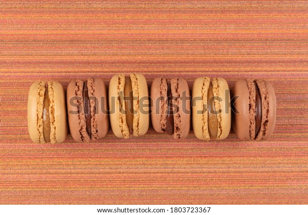 Six coffee and chocolated flavoured macaroons on red vinyl background.