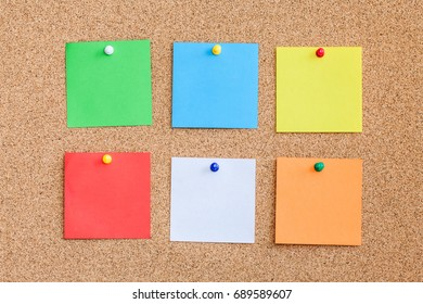 Six color memo reminder cards pinned to cork board. Blank empty copy space square papers background.