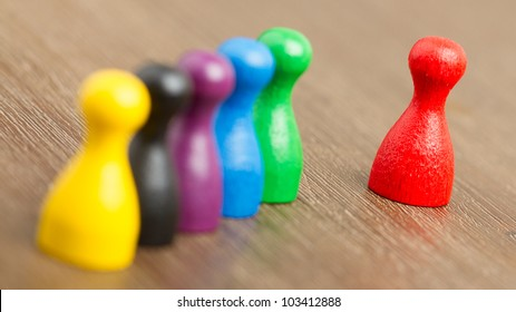 Six colored pawns isolated on a wooden background