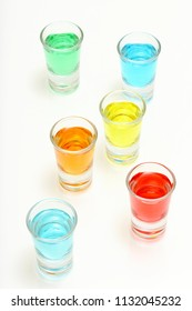 six colorful cocktail shots on white