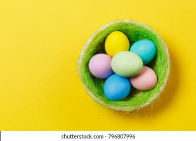 Six colorful pastel monophonic painted Easter eggs in basket with green grass isolated on yellow background. Happy Easter concept. Copy space for advertisement. With place for text. Top view on eggs