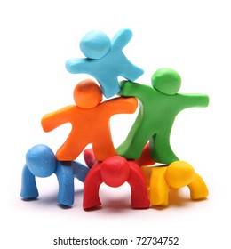 six colorful plasticine guys making a human pyramid