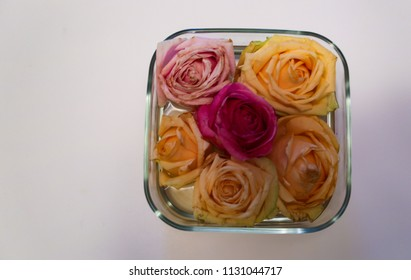 Six colorful roses are lying in a bucket of glass. Four roses are yellow, the top right rose is light pink and the middle rose is in a strong pink.