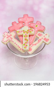 Six (cross shaped) pink cookies on small cake stand