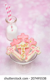Six (cross shaped) pink cookies on small cake stand with milk bottle and two straws. Shot with copy space.