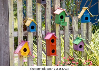 Six cute little birdhouses on rustic wooden fence.