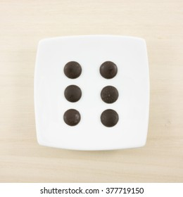 The six dark chocolate buttons and small white square disk on light brown wooden board.