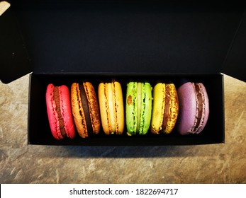 Six different colors macarons cookies in a black box