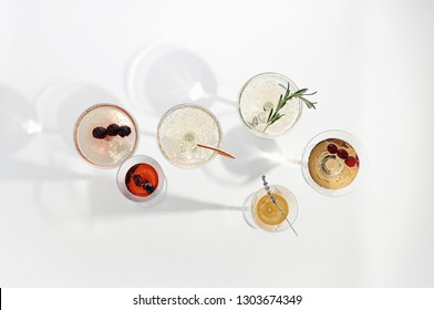 Six easy Champagne cocktails on white background. Top view of six sparkling wine drinks with copy space
