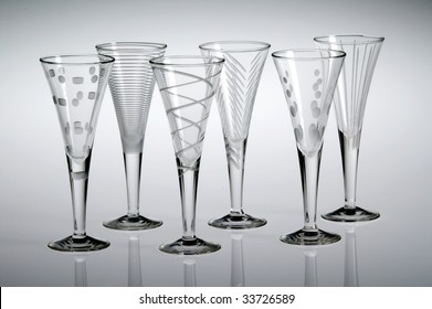 Six empty etched crystal liqueur glasses, with a gray background.