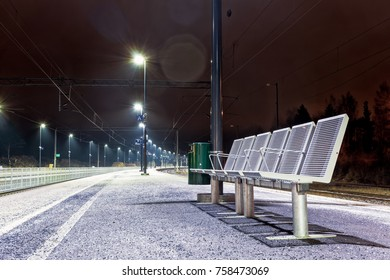 Six empty seats at the railway station of a small town in the Northern Finland on a winter night.