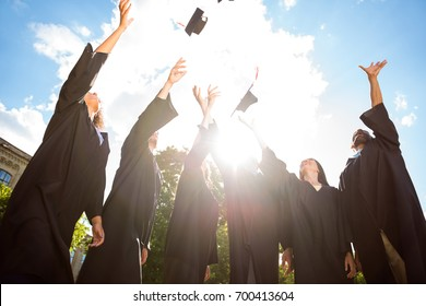 Six excited successful graduates in black robes are throwing up their mortar-boards with red tassels all together. They did it, passed exams, finished course of studies, got the degree