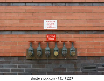 Six firepump test headers on red brick wall, for testing the flow capacity of fire pumps