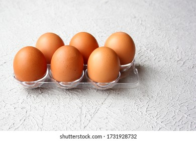 Six fresh brown chicken eggs in a plastic package. Close-up.