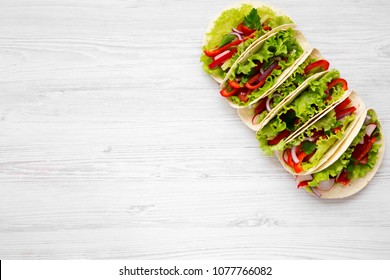 Six fresh vegetarian tacos on white wooden background. From above. Top view. Copy space