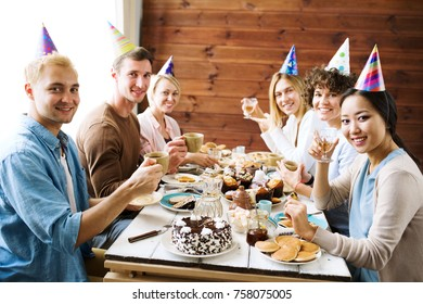 Six friends in birthday caps looking at camera during gathering by festive dinner