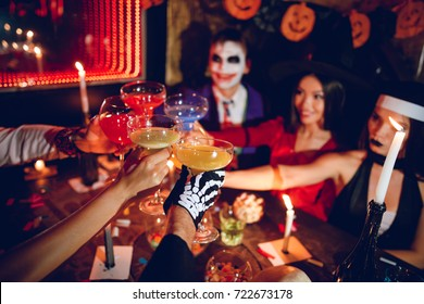Six friends rest in a nightclub and sit at a table with colored cocktails. They have different sweets on the table. Everyone is having fun