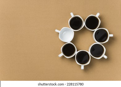 Six full and one empty white porcelain coffee cups making a circle