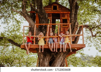 Six funny colourful barefooted kids playing up on a tree house in summer near the river