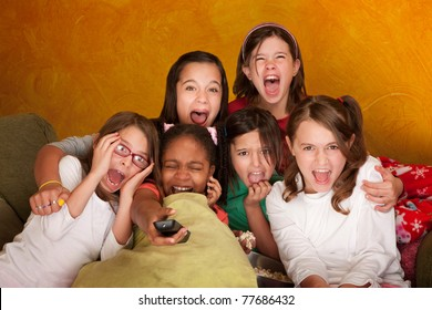 Six girls watching a movie scream at a sleepover