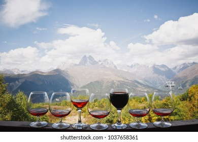 Six glasses of cognac and one glass of red wine stand against the backdrop of a beautiful mountain landscape and cable car. There are white clouds in the blue sky.