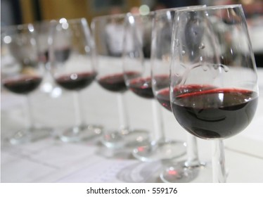 Six glasses in a row at a wine tasting, filled with bordeaux