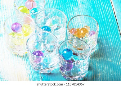 six glasses for vodka filled with colorful rubber balls, light blue background