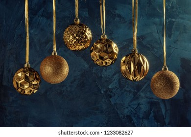 Six golden Christmas balls hanging on ribbons, on a dark blue background with textures and decorative putty. Copy space. Festive layout with place for text.
